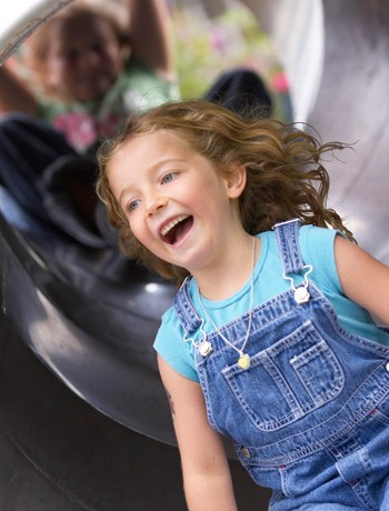young girl laughing on a slide in a playground